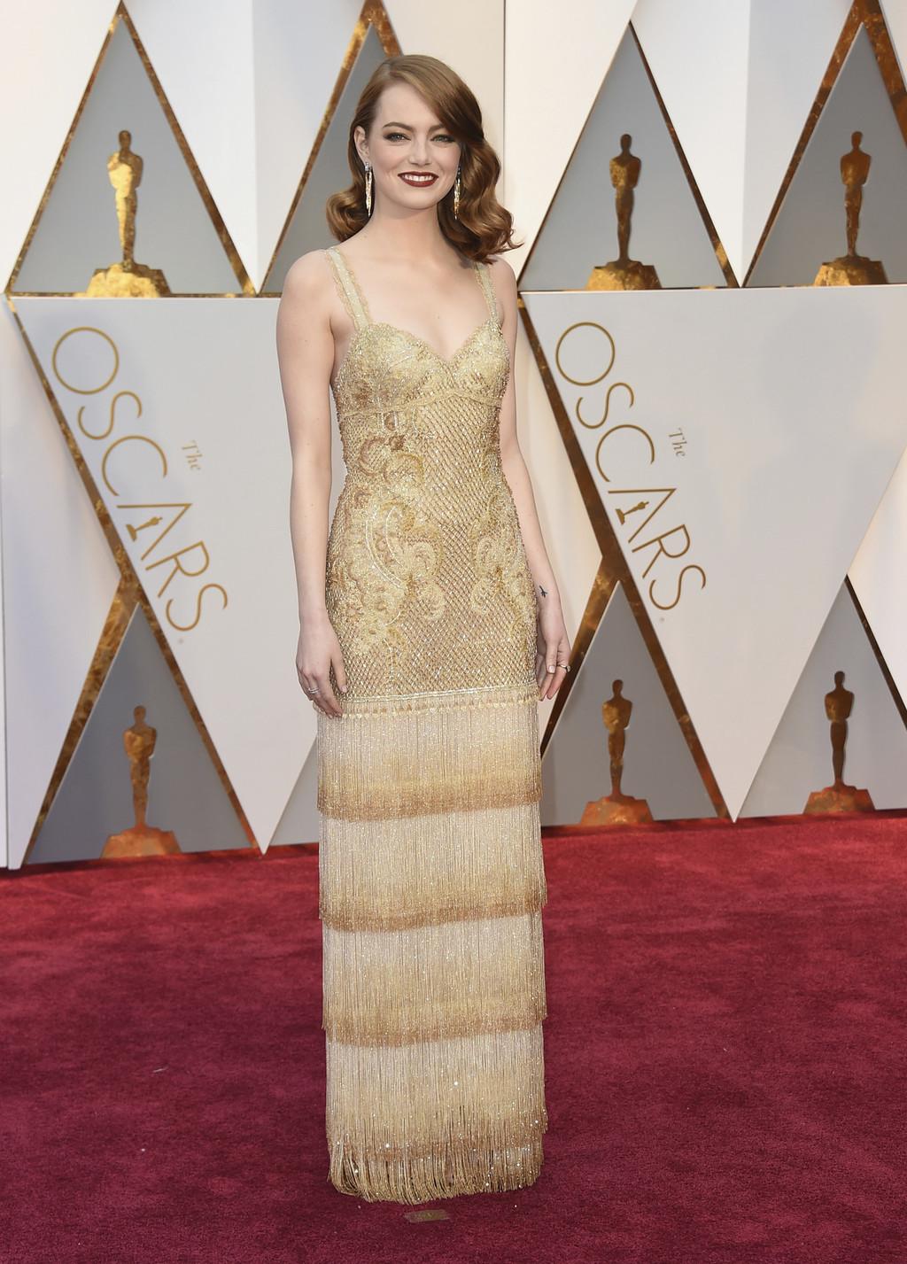 Emma Stone con un vestido de color dorado y un peinado modesto