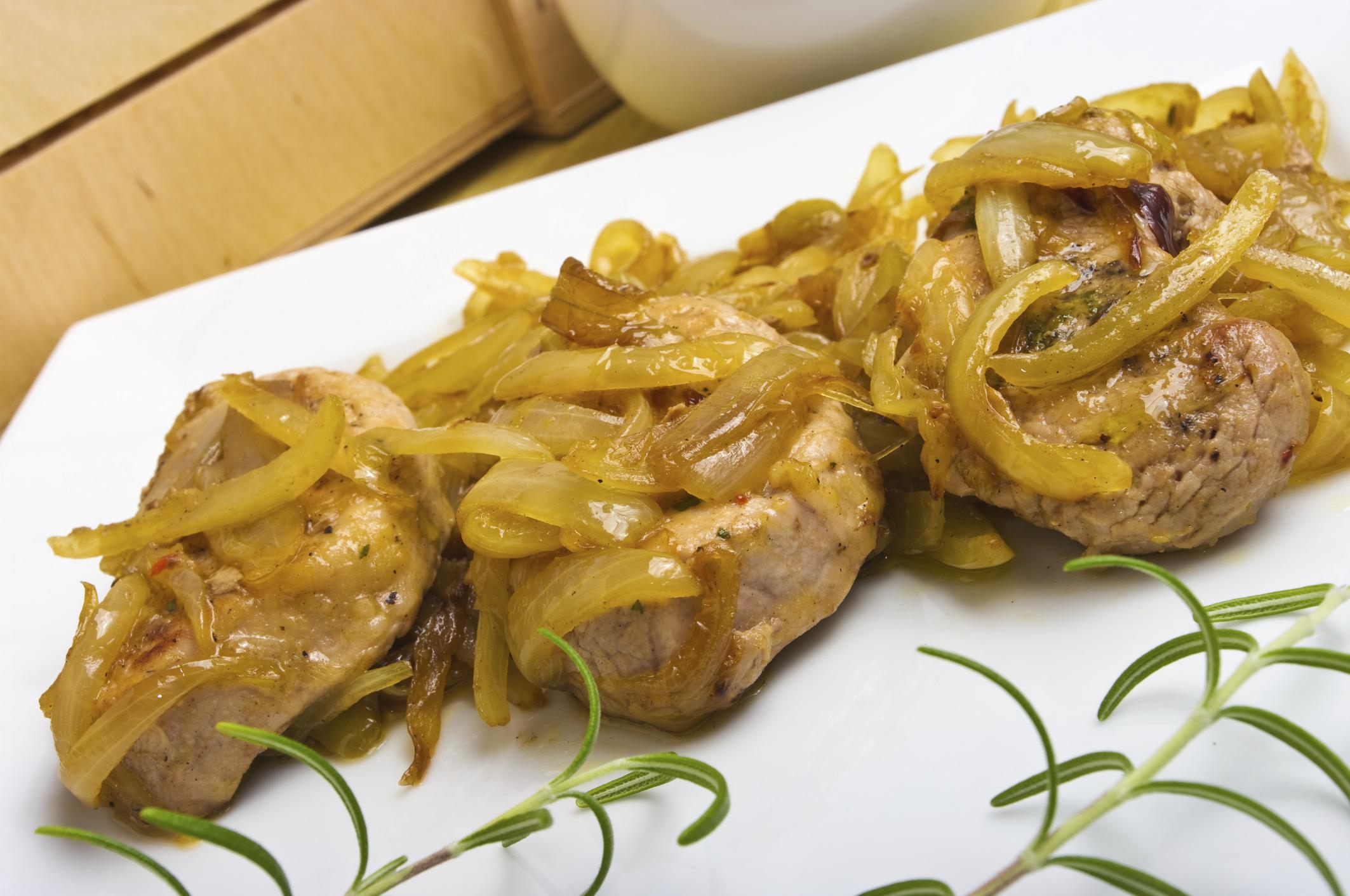 en una sartén se coloca un poco de aceite de oliva y se pone la cebolla cortada en aros, bien ordenadas, se pinchan con un tenedor,  se les añade  una cucharada de azúcar.