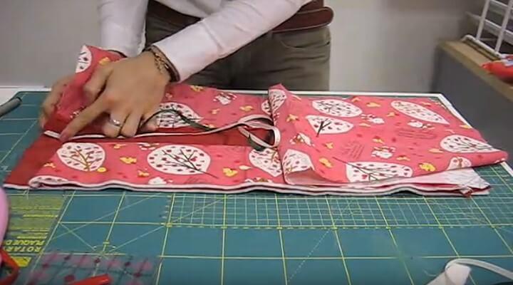 cinta para cerrar la La pieza de tela larga con la guata y el forro, la poneis en la parte de arriba, afianzandolo con alfileres y encima lo encarais con el otro trozo de tela grande.